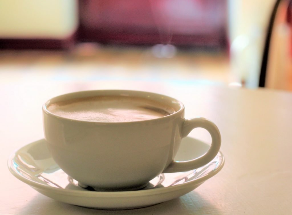 A lone cup of coffee on a cafe table